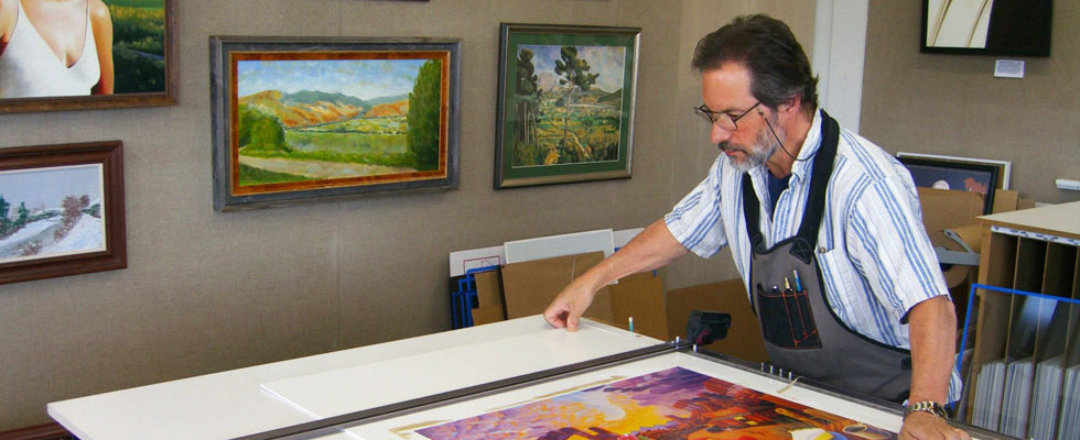 owner joseph guggino framing a picture